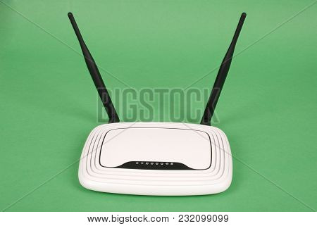 White Wi-fi Router With Two Antennas Isolated On Green Background