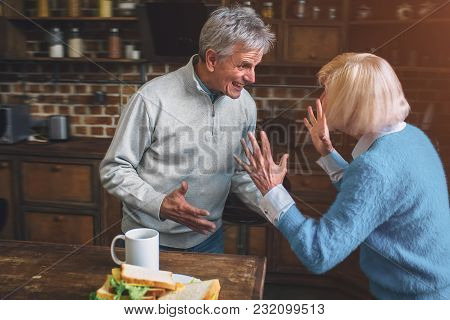Funny Picture Of Old Grandma Standing With The Grandpa And Talking To Him. She Is Emotional And Doin