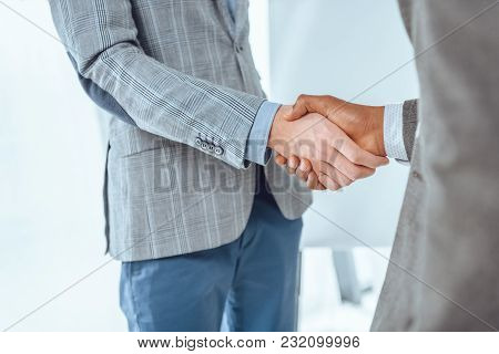 Cropped Image Of Two Businessmen Shaking Hands At Office Space
