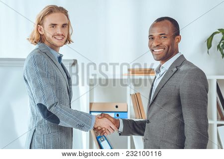 Two Businessmen Shaking Hands At Office Space