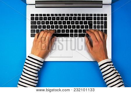 Woman Hands Typing On Laptop Computer On Blue Background.