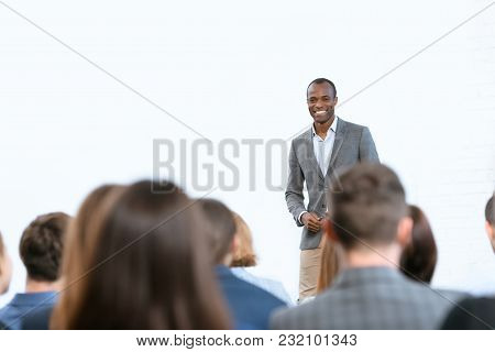 Smiling African Man Standing Against Copy Space At Meeting