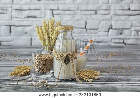 Homemade Vegan Milk Of Sprouted Wheat In A Glass Bottle, Spikes And Grains Of Wheat