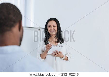 Smiling Female Psychoanalyst Taking Notes While Standing At Whiteboard In Office