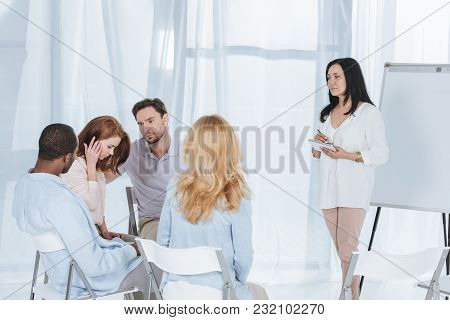 Middle Aged Multiethnic People Supporting Each Other While Psychotherapist Taking Notes During Group