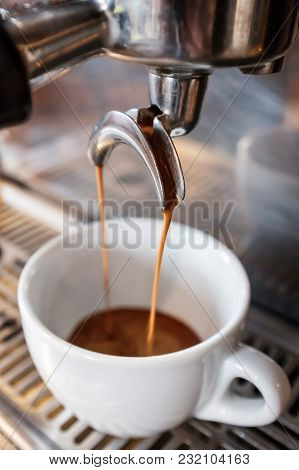 Fresh Espresso Dripping From Portafilter Of Coffee Machine Into White Cup