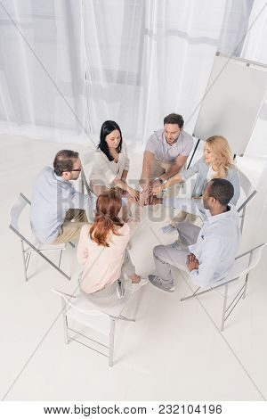 High Angle View Of Multiethnic Middle Aged People Sitting On Chairs And Stacking Hands During Group