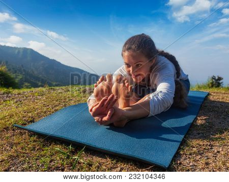 Woman doing Ashtanga Vinyasa Yoga asana Paschimottanasana seated forward bend pose asana in mountains