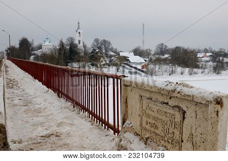View On A Village With Church Covered By Snow And A Bridge Over A Small River Built To Commemorate 5