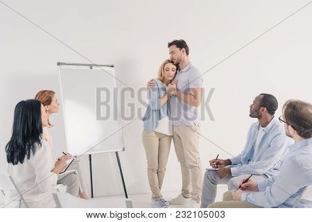Middle Aged Couple Holding Hands While Standing Near Blank Whiteboard And Other People Sitting On Ch