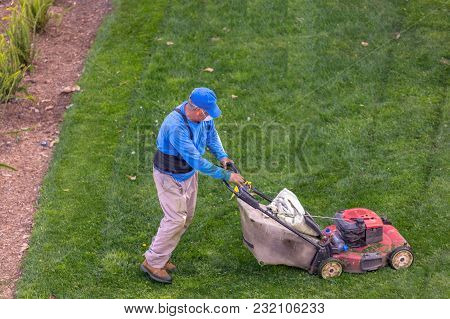 A Gardener Mowing Lawn High Angle View