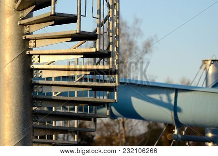 Detail Of Spiral Stairs To Blue Water Slide At Sunset