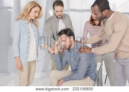 Mid Adult Multiethnic People Supporting Upset Man During Group Therapy