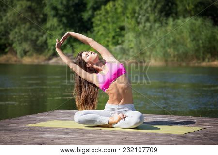 Young, Beautiful Girl Performs Yoga Asanas On The Lake Shore. Nature, Zen, Lifestyle