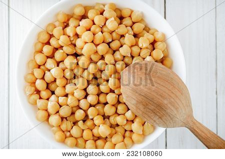 Cooked Chickpeas In A Bowl And A Wooden Spoon On A White Table, Top View. Healthy Vegetarian Food