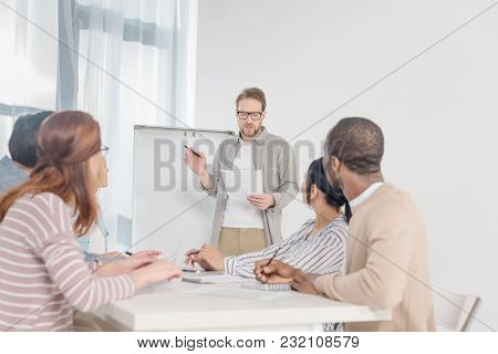 Middle Aged Man In In Eyeglasses Holding Paper And Having Conversation With His Team While Standing