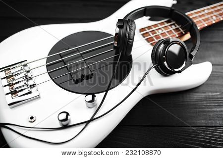 Black Headphones And White Bass Guitar On The Black Wooden Background