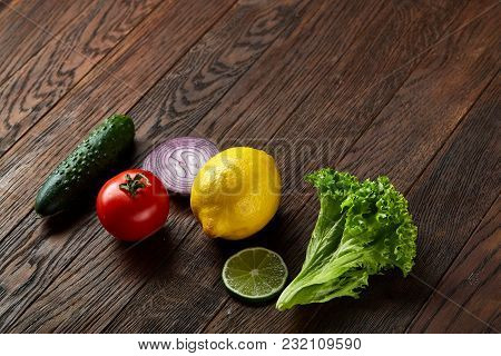 Fresh Vegetables Still Life. Cucumber, Tomato, Onion, Lemon, Lime And Lettuce Lined Up On A Wooden B