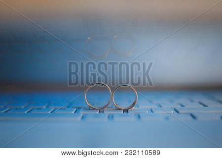 Wedding Rings On The Keyboard Of Notebook Computer. Love Concept. Text Space