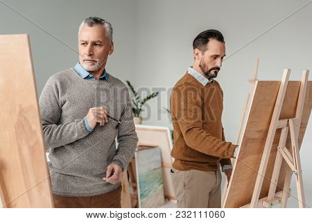 Two Adult Male Artists Painting On Easels In Art Studio
