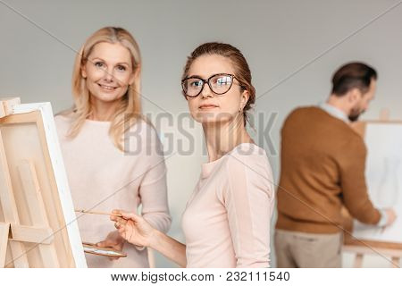 Beautiful Middle Aged Women Looking At Camera While Painting Together At Art Class
