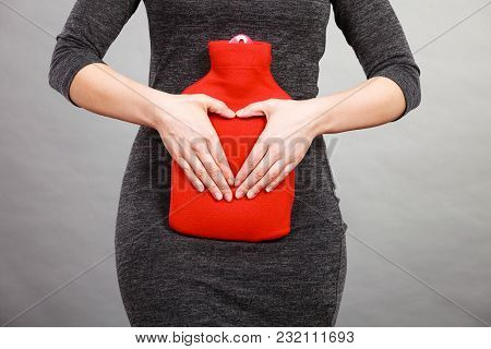 Unrecognizable Woman Having Stomach Ache, Holding Hot Red Water Bottle On Abdomen As Remedy For Pain