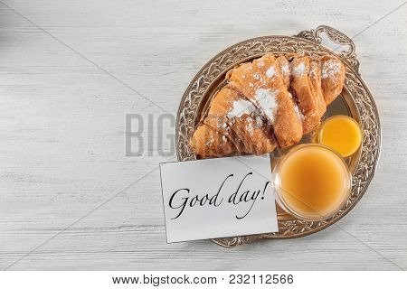 Glass of juice, croissant and card with words