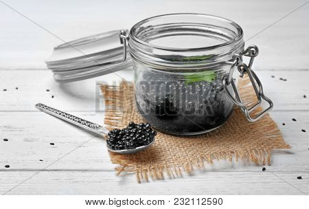 Jar and spoon with delicious black caviar on table