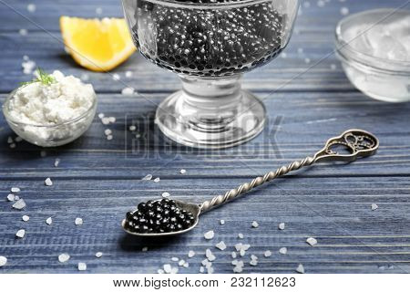 Spoon with delicious black caviar on table