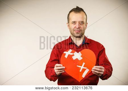 Bad Relationships, Breaking Up, Sadness Emotions Concept. Adult Man Holding Broken Heart, On Grey