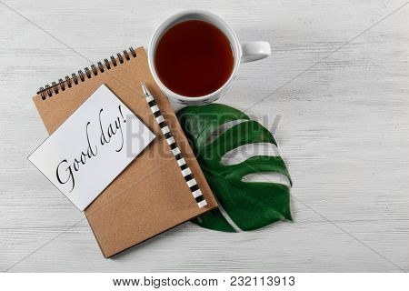 Cup of tea for breakfast, notebook and card with words