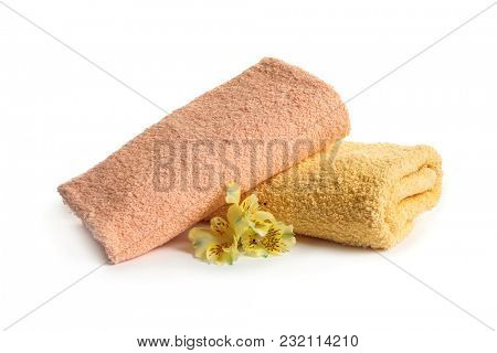 Folded clean terry towels and beautiful flowers on white background