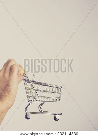 Male Hands Holding Empty Shopping Basket Cart, Toned Image On Grey. Seasonal Sales, Boxing Day Conce