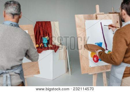 Back View Of Two Men Painting Still Life On Easels At Art Class