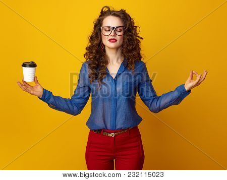 Relaxed Trendy Woman With Long Wavy Brunette Hair With A Coffee Cup In Yoga Pose Against Yellow Back