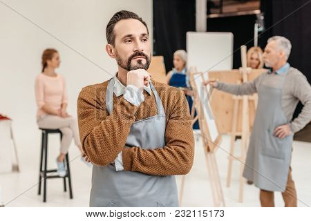 Pensive Bearded Artist In Apron Looking Away While Adult Students Painting At Art Class