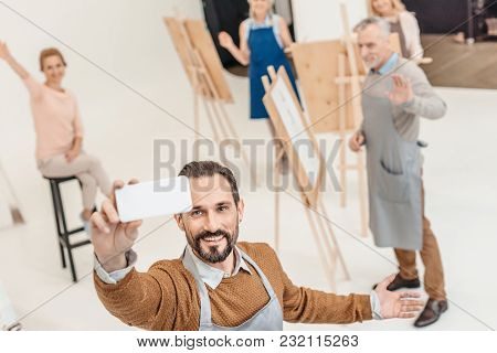 Mature Man With Smartphone Taking Selfie With Adult Students At Art Class