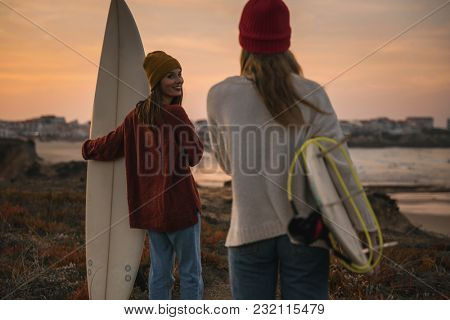 Shot of two female friends holding their surfboards while looking to the ocean