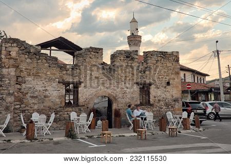 NOVI PAZAR, SERBIA - AUGUST 12, 2017: clients sitting on sidewalk of a coffee bar in the old turkish quarter; on background minaret of a mosque against sky at sunset