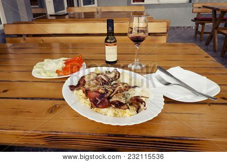 BAR, MONTENEGRO - AUGUST 14, 2017: dish of grilled squid with rice and potatoes and onion garnish in a fish restaurant