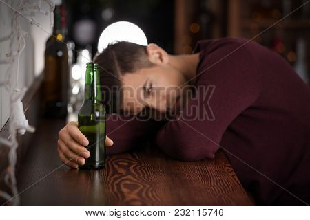 Young man with bottle of beer in bar. Alcoholism problem