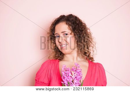Beautiful Curly Woman Smiling Behind Flowers. Selective Focus. Hello Spring Concept.