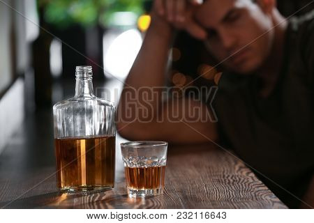 Glass and bottle of drink and blurred man on background. Alcoholism problem
