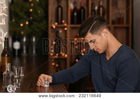 Young man with glass of drink in bar. Alcoholism problem