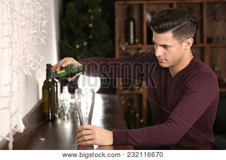 Young man pouring beer into glass at bar. Alcoholism problem