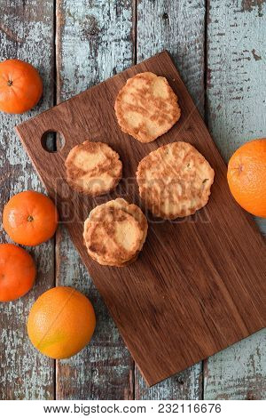 Homemade Imperfect Citrus Cookies With Raw Oranges And Clementines On Cutting Board On Shabby Blue W
