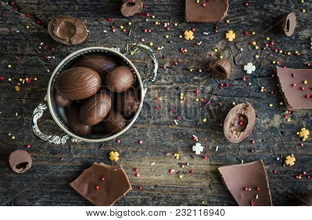 Easter Composition With Chocolate Eggs On Old Rustic Wooden Background. Happy Easter Concept. Top Vi