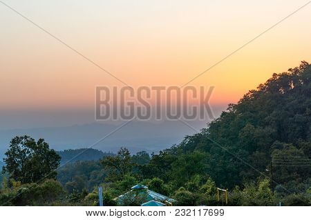 Dusk Shot With Beautiful Orange Sky, Tree Covered Hills, A Small Shed. Perfect Shot To Showcase The