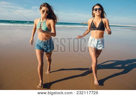 Two beautiful female friends in bikini running at the beach and having fun together
