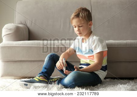 Little diabetic boy taking blood sample with lancet pen at home